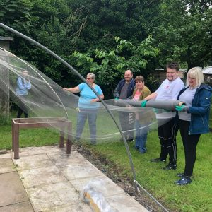 Service users of Old Tree Nursery installing ClearMesh onto poly tunnel